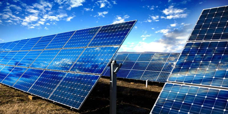 Row of photovoltaic solar panels and sky background